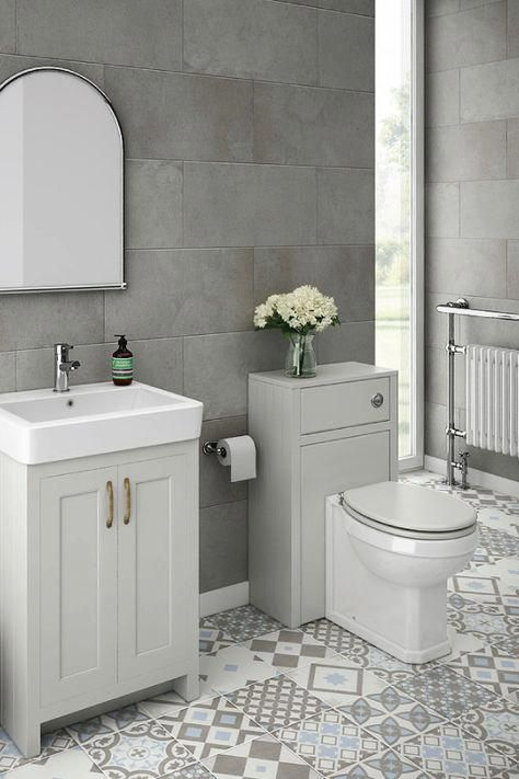 bathroom with white toilet, white cabinet, white sink, mirror, grey and white pattern tiles with different color and patterns