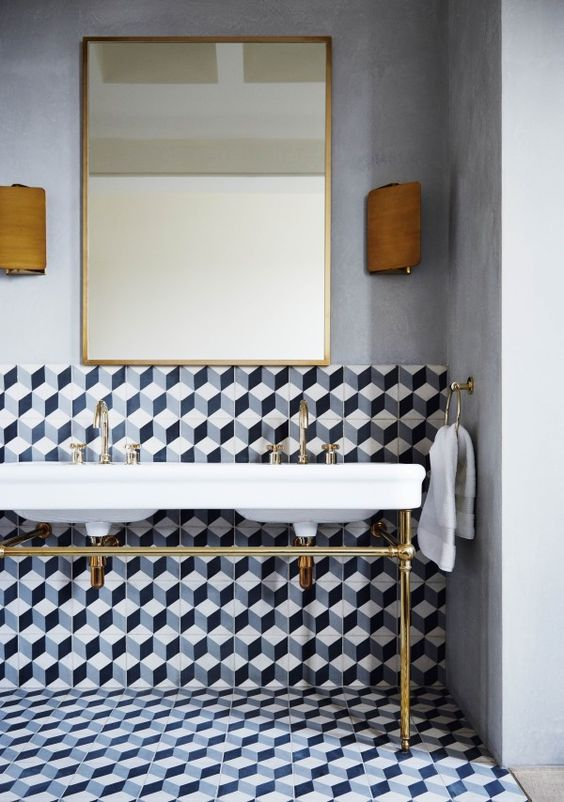 bathroom with white wall, large square mirror, sconces, monochrome little hexagon tiles on the floor and some of the walls, white double sinks with golden lines