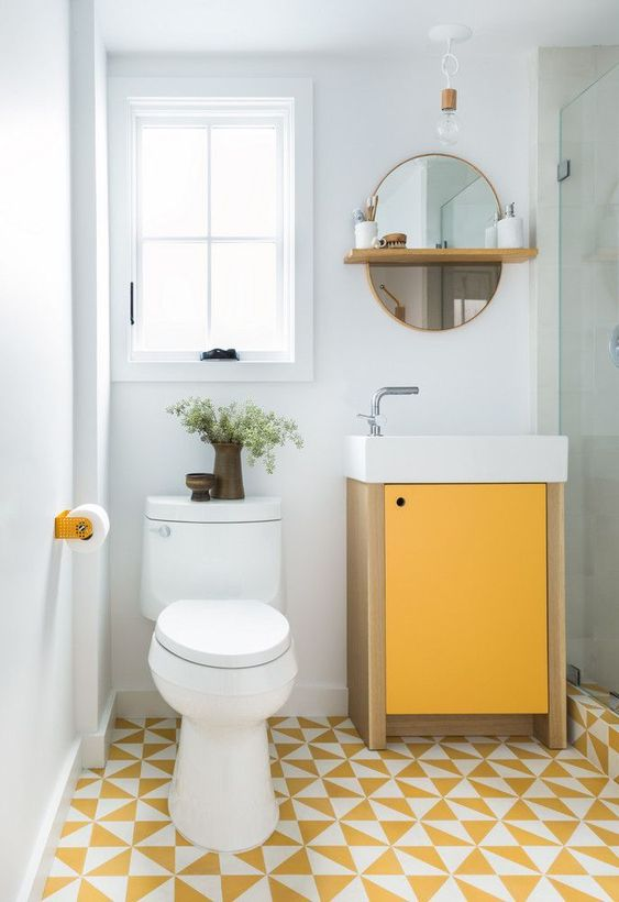 bathroom with white wall, white framed window, mirror, shower area with glass partition, yellow white tiles floor, white toilet, yellow tissue holder, yellow cabinet with white sink