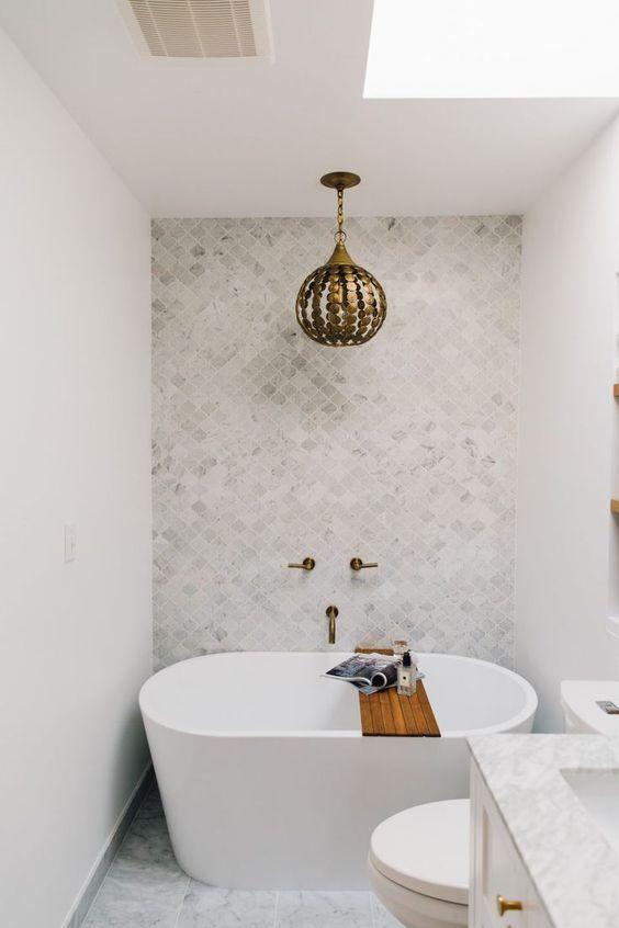 bathroom with white wall, white marble floor, white tiels accent wall, golden pendant, white bathtub, white toilet, white vanity