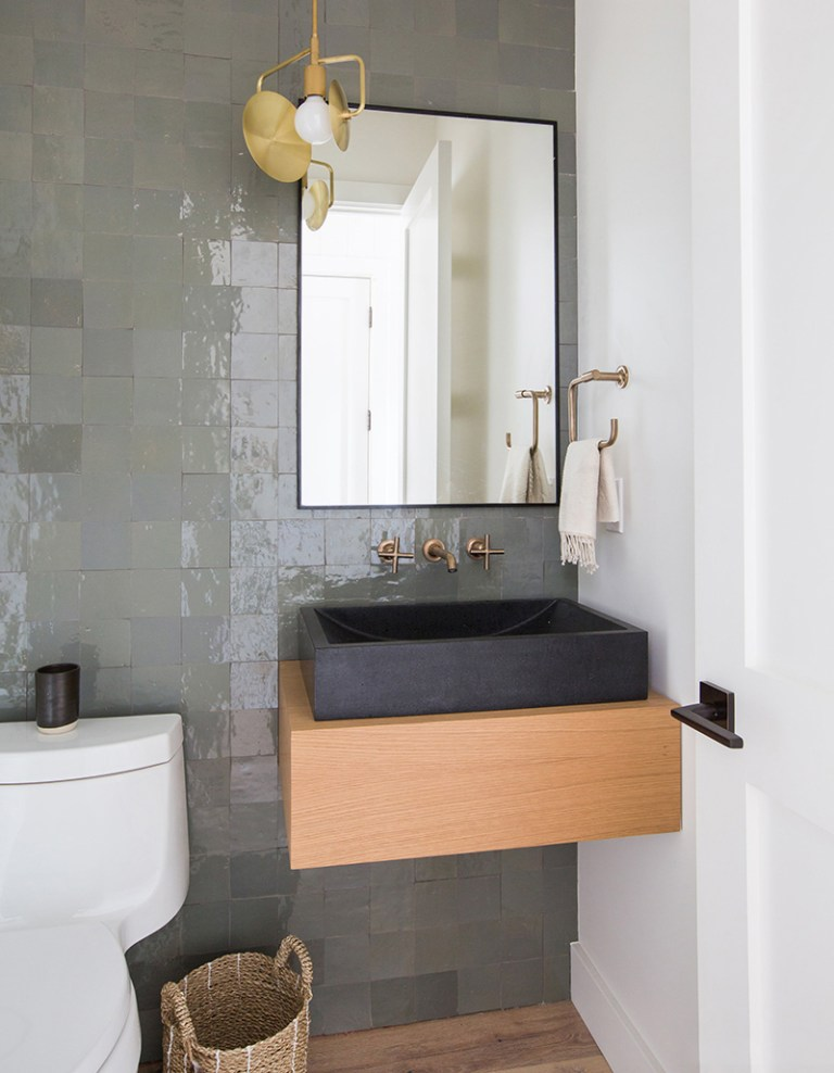 bathroom with white wall, white toilet, wooden floor, wall tiles wall, wooden vanity, grey sink, golden faucet, square mirror