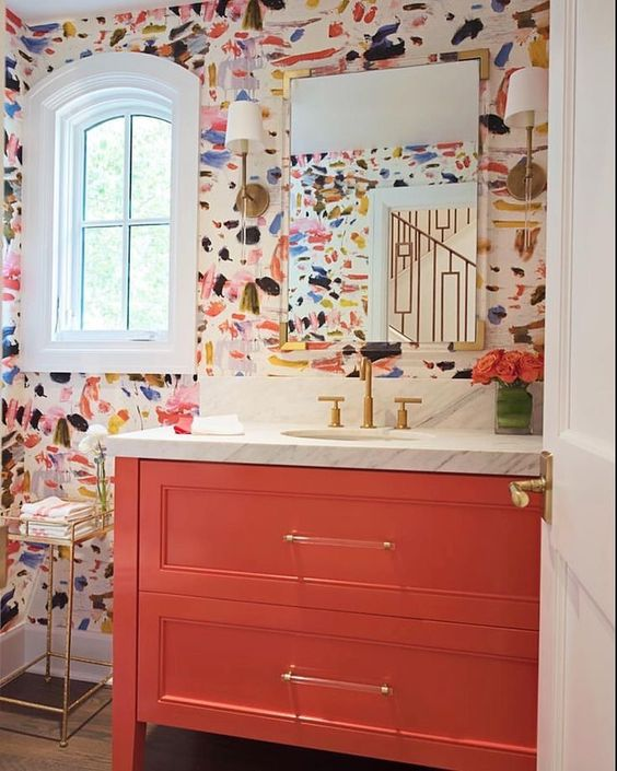 bathroom with wooden floor, shelves, colorful abstract wallpaper, white framed window, white marble vanity with sink, golden faucet, glass wall