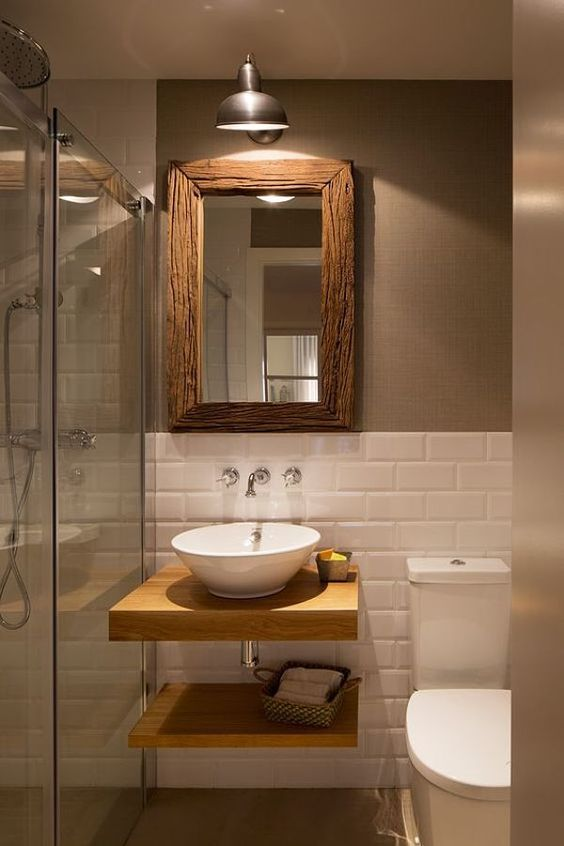 bathroom with wooden floor, white painted open brick half bottom of the wall, grey wall on top half, white toilet, wooden floating vanity and shelves, white sink