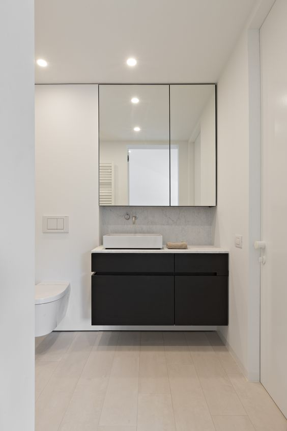 bathroom with wooden floor, white wall, black floating cabinet with white top, white sink, mirror, white toilet