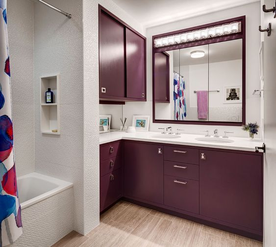 bathroom with wooden floor, white wall, white marbled wall, long purple cabinet, long mirror with lampps on top, purple cabinet above