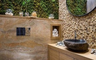 bathroom with wooden floor, wooden floating cabinet vanity, textured brown backsplash, brown marble wall, plants on top