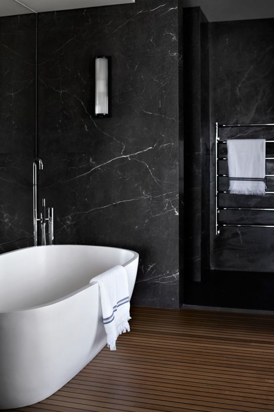 bathroom with wooden plank flooring, white tub, black marble wall
