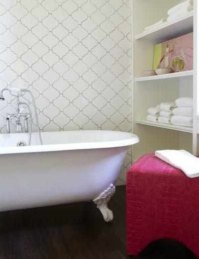 bathroom withwooden floor, pink stool, white tub, white arabesque tiles on the wall, white shelves