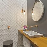 Bathroom Wtih Textured Wall And Floor, Grey Painted Wall, Round Mirror, Brown Wooden Top With Grey Marble Sink, Sconce, Grey Toilet