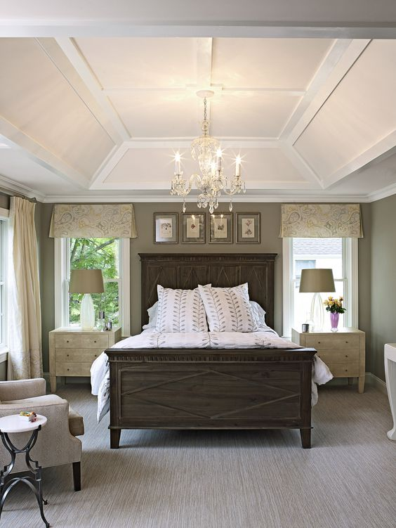 bedroom, grey flooring, dark wooden bed platform, muted green wall, chair, side table, side cabinets, table lamps, chandelier, tray shed ceiling