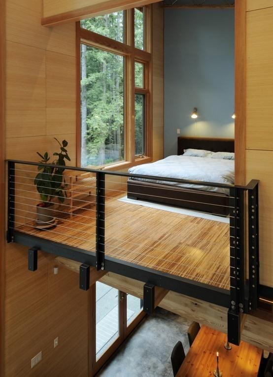 bedroom on the upper loft with bamboo floor, wooden bed, plants indoor, large glass window