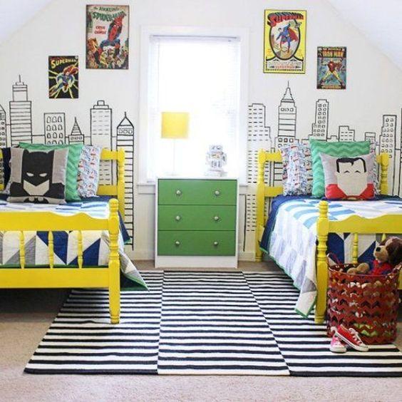 bedroom with beige floor, striped rug, yellow beds, white blue linen, superhero pillows, superhero posteres, city wallpaper