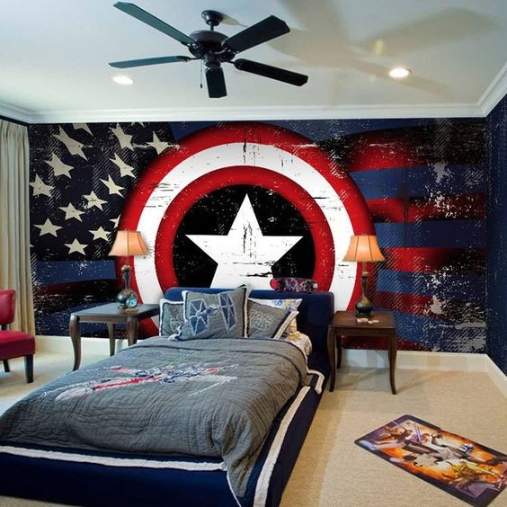 bedroom with beige rug, blue bed, grey linen, captain america logo wallpaper on the accent wall, side tables, table lamp, black ceiling lamp