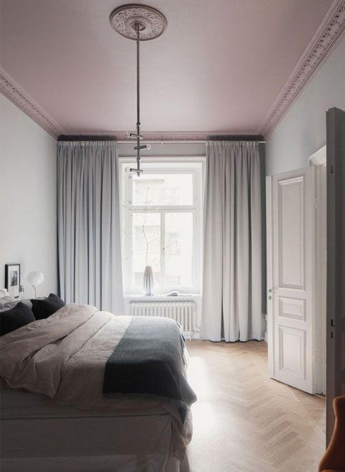 bedroom with chevron pattern, white platform bedding, white wall, white curtain, white wooden door, pink painted ceiling