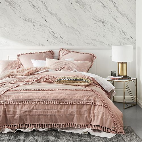 bedroom with grey floor, grey rug, pink bedding, pink pillows, white bedding, marble wall, whiteheadboard bed