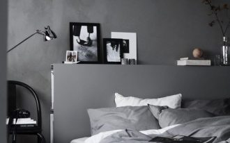bedroom with grey wall, grey wooden floor, gey headboard, grey linen, black chair, silver floor lamp