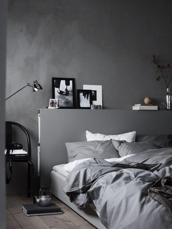 bedroom with grey wall, grey wooden floor, gey headboard, grey linen, black chair, silver floor lamp