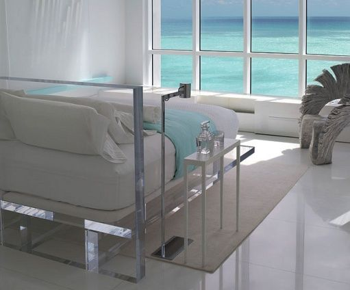 bedroom with marble tiles, white rug, acrylic bed with white bedding, windows