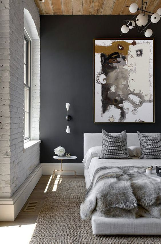 bedroom with rattan rug, wooden floor, white beddin, grey pillows, grey accent walls, white pendants, white bare bricks wall