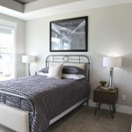 Bedroom With Rug Flooring, Metal Platform Bed, Grey Bedding, White Wall, Coffer Ont He Ceiling, Wood On The Inside