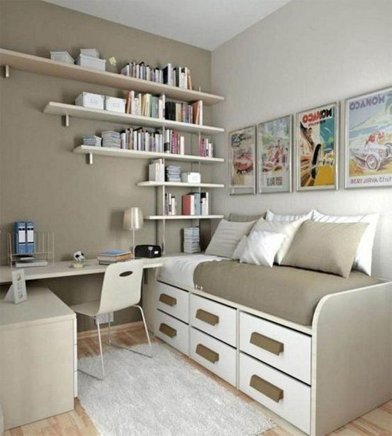 bedroom with wooden floor, brown wall, white floating wooden book shelves, beige study table with chair, platform bed with two levels of drawers