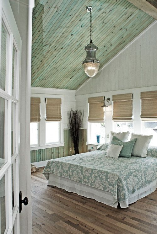 bedroom with wooden floor, green bedding, white wooden wall, windows with bamboo shades, gren wooden ceiling with pendant
