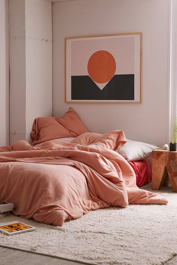 bedroom with wooden floor, pink rug, bed without platform, pink cotton bedding, pictures on white wall