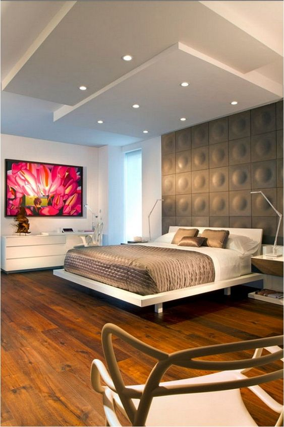 bedroom with wooden floor, white platform bed, brown bedding, white cabinet, grey accent wall with round motives, white ceiling with lamps and different level of boards