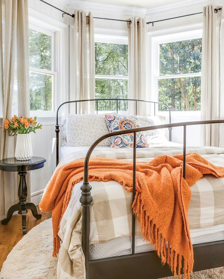 bedroom with wooden floor, white rug, metal bed platform with white bedding, pattern pillows, flowers, windows, curtains, orange blanket