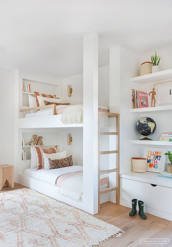 bedroom with wooden floor, white rug, white bunk bed with shelves on each headboard, wooden stairs, white big shelves on bed end