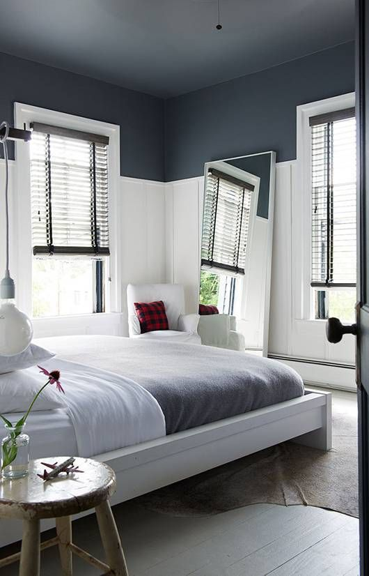 bedroom with wooden flooritn, white bed platform with grey bedding, mirror, white chair, shade ont he windows, grey painted ceiling