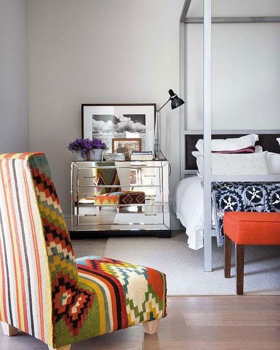 bedroom, wooden floor, white rug, colorful tribal pattern white bedding, mirrored side cabinet, tribal blanket, orange bench