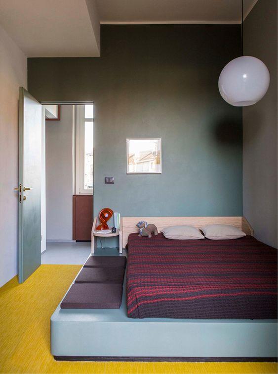 bedroom, yellow floor, blue bed platform, purple seating pillow, grey wall, white globe pendant
