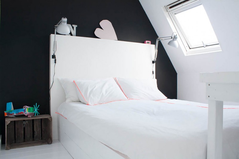 bedside table height black and white walls white bed white headboard white wall sconces skylight white floor white bedding wooden table white pillows