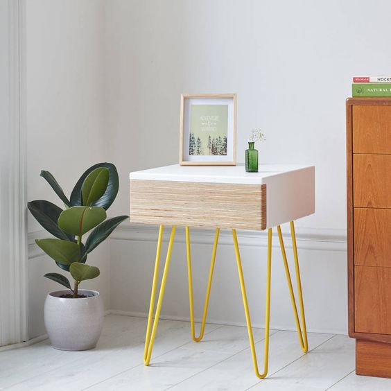 bedside table with white top finish, one wooden drawer, yellow thin mire feet