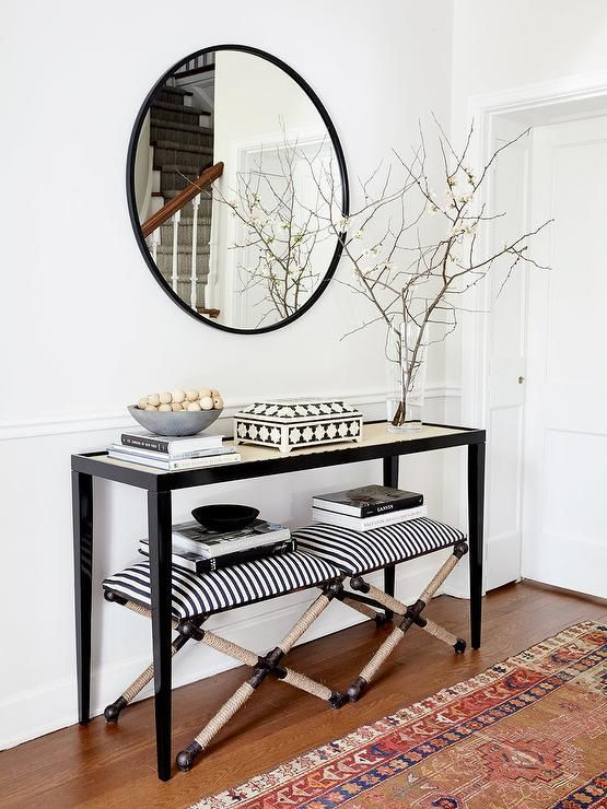 black wooden console table with glass top, two chairs with stripes cushion, books, decoration, round mirror