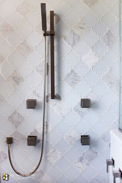 blue arabesque tiels wall on the shower with dark colored metal shower