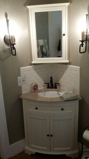 brown marble top with white sink corner triangle vanity with white wooden cabinet, white tiles backsplash, mirror with triangle storage behind