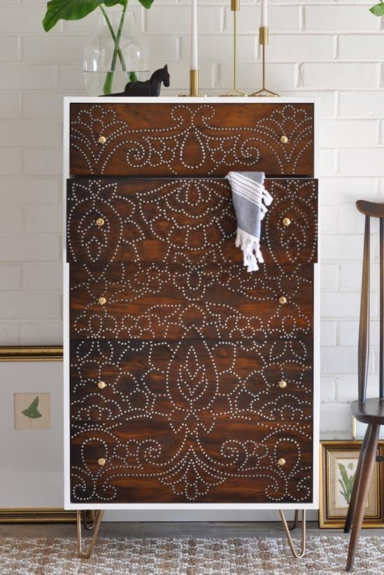 brown wooden cabinet with tribal stencile pattern, white wall