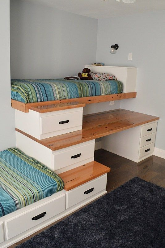 bunk beds with unique sacks, one bed in the left, the other in the top right with staris and cabinet, and table in between