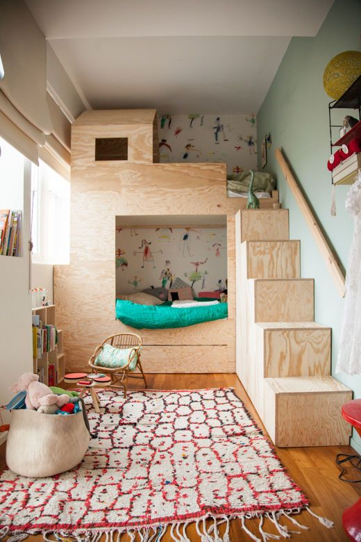 bunkbed with wooden boxes liek castle, with stairs, in a room with wooden floor, rug, shelves, chairs