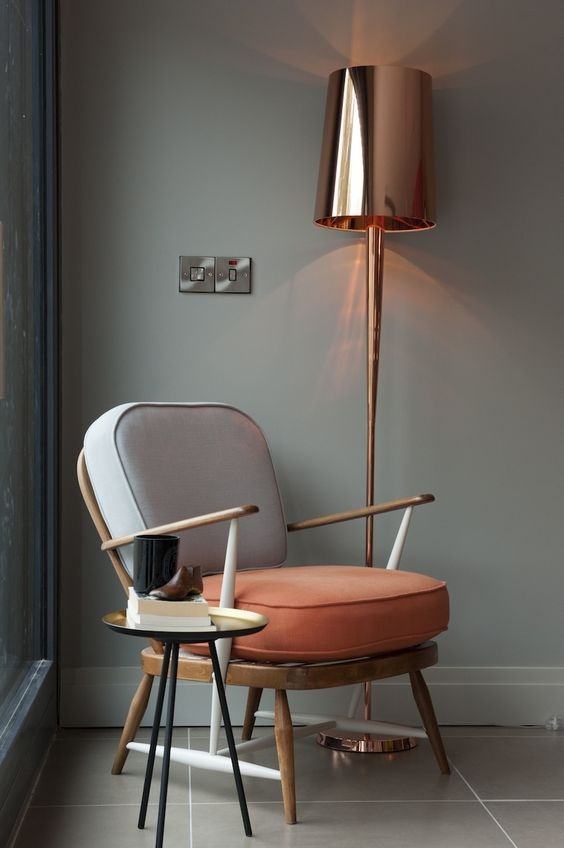 chair with orange seating, grey back cushion, wooden material, small round black table, golden tall floor lamp