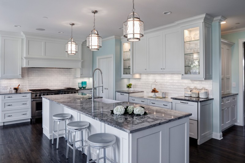 coastal light fixtures white cabinets white island dark wooden floor pendant lamps white subway backsplash marble countertop grey stools stovetop range hood shelves sink