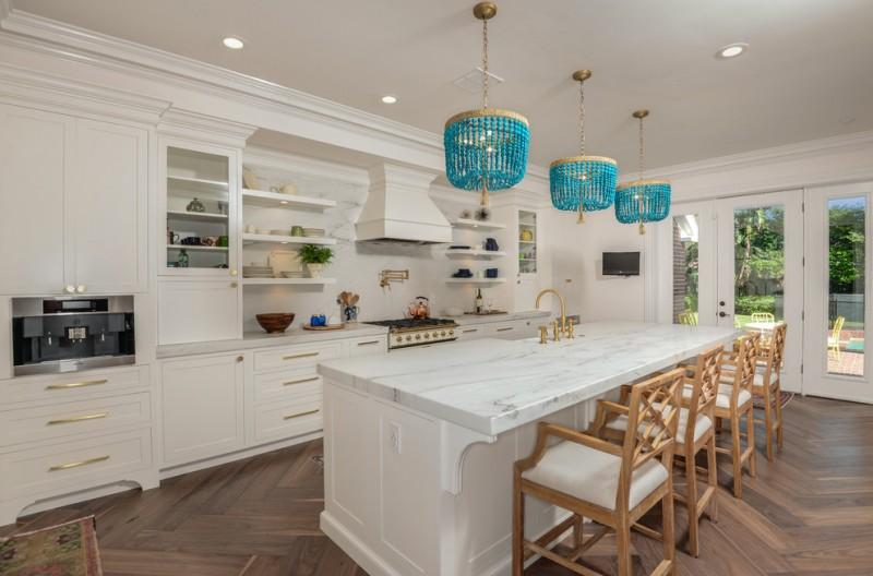 coastal light fixtures wooden chairs white island white cabinets built in kitchen appliances range hood stovetop blue pendant white countertop wooden herringbone floor gold