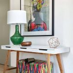 Console Table With Brown Wooden Feet, White Wooden Top With Three Drawers, Green Glass Lamp With White Cover, Picture, Colorful Ottoman