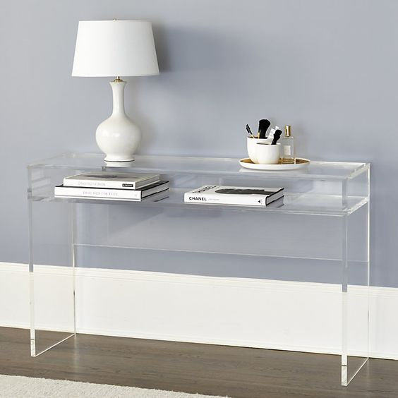 console table with clear acryllic, books, white table lamp