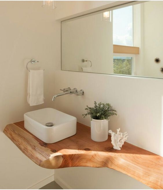 corner bathroom with white wall, grey floor, wooden floating vanity, white small square sink with silver faucet, mirror, towel rack