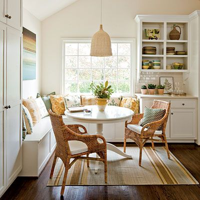 corner dining nook with white bench, rattan chairs, pillows, rattan pendant, white shelves on the side