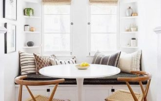 corner dining nook with white bench with cushions and pillows, white round table, brown rattan chairs, built in small corner shelves on two corner, windows