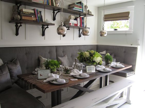 corner dining nook with white wooden bench, grey cushion, long wooden table, brown wooden shelves on white wooden wall, three little pendants